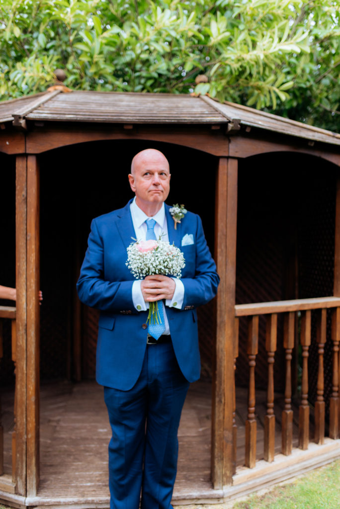 funny groom posing with flowers