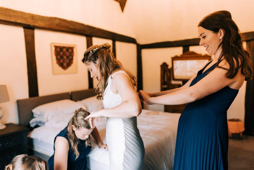 Bridesmaids help bride get into eco friendly wedding dress