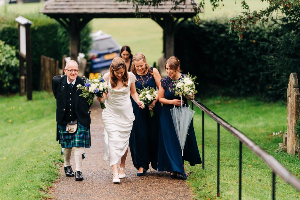 Bride and bridesmaids walk to the ceremony in the rain