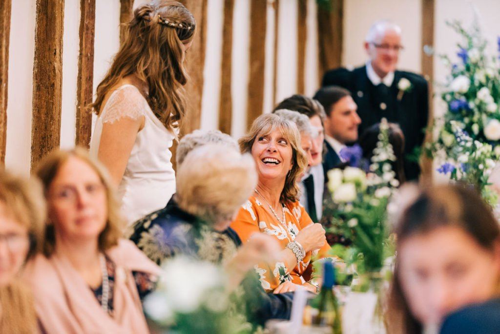 Bride talks to wedding guests during wedding breakfast