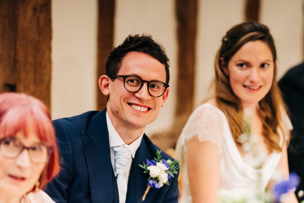 Groom smiles at guests