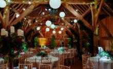 barn wedding venue decor lights rustic greenery