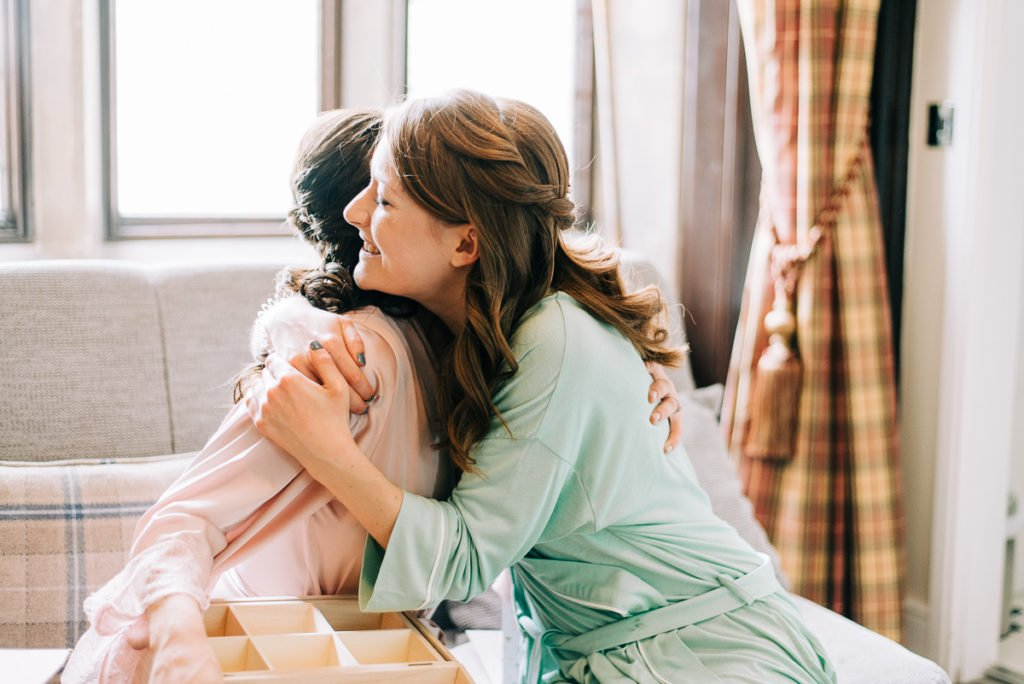 Bride and maid of honour hugging