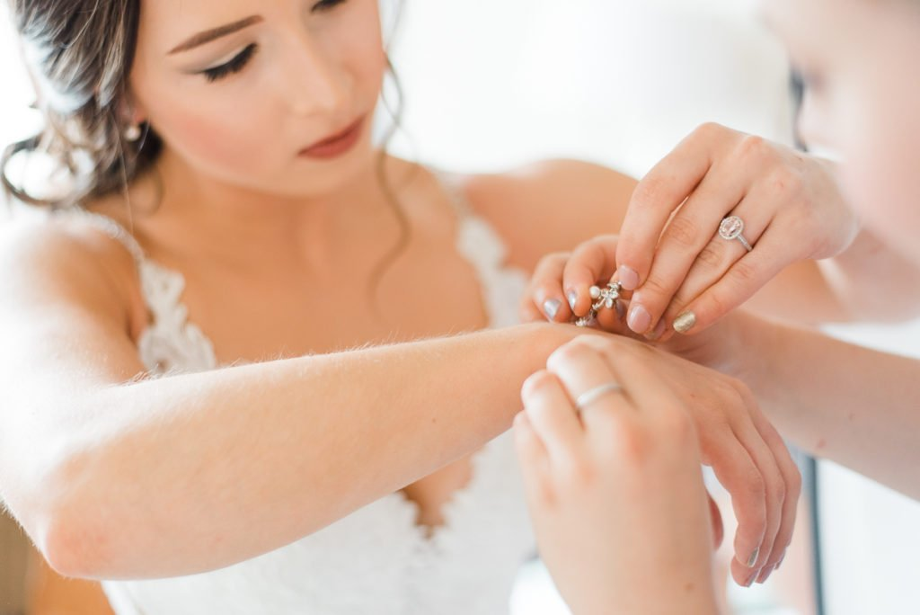 Bride puts on jewellery as the finishing touches