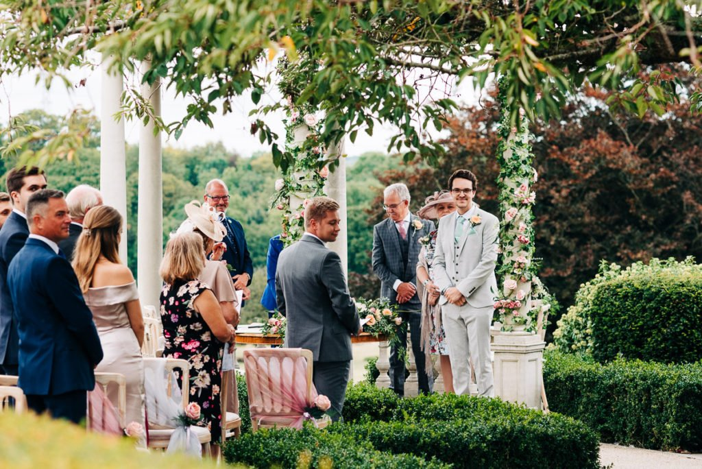Groom waits nervously for his bride outdoor wedding ceremony