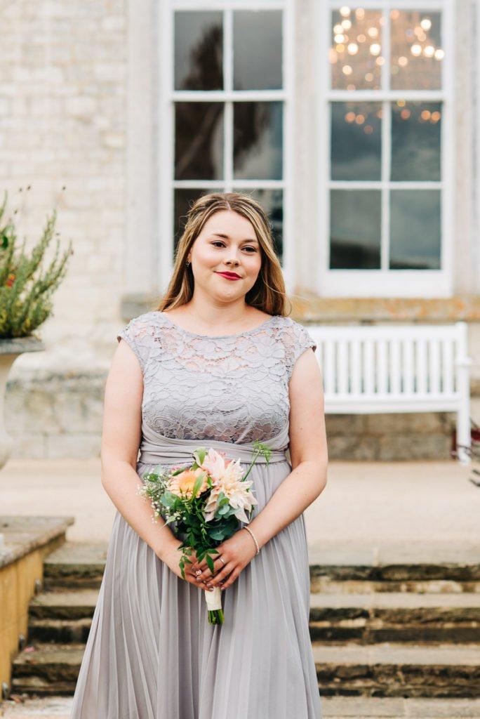 Bridesmaid enters wearing a grey dress