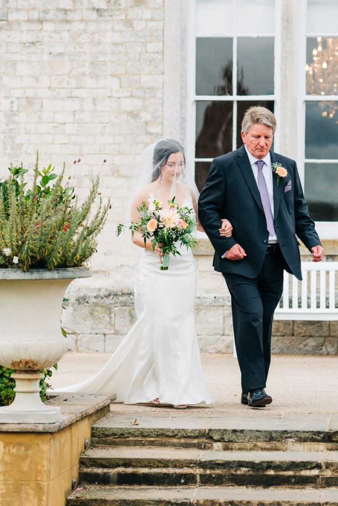 Bride enters the ceremony with her dad walking her down the aisle
