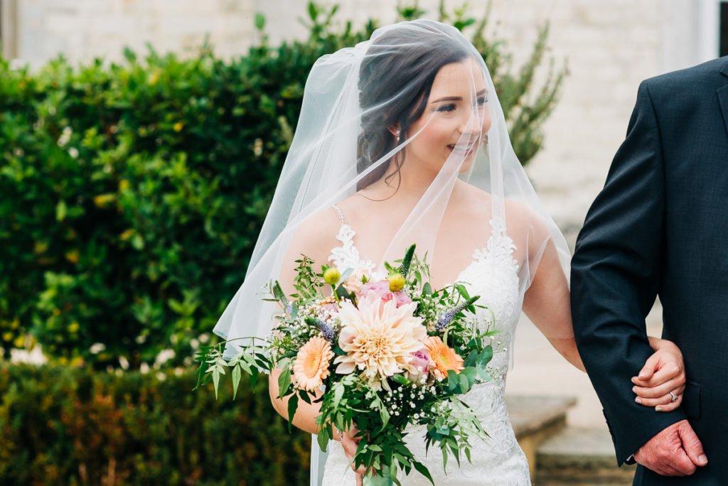 Bride smiles underneath her veil