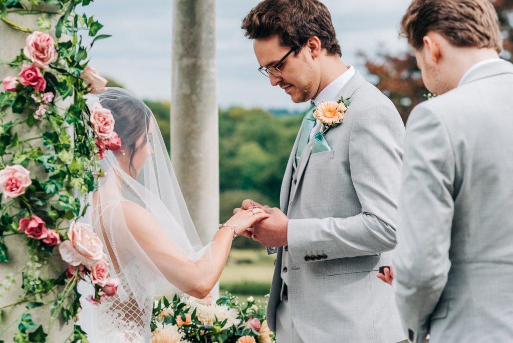 Groom puts wedding ring on bride