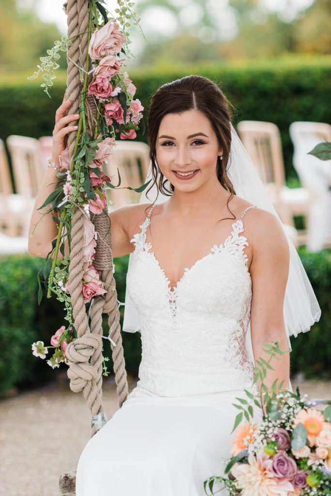 Stunning bride sits on a swing decorated with flowers
