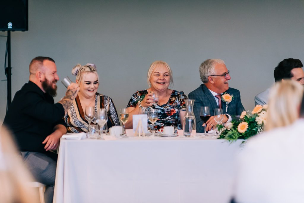 Family and friends laugh at the wedding speeches, candid photography
