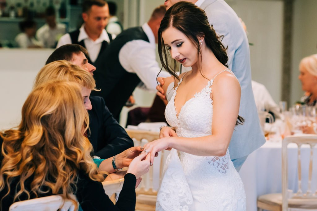 Bride shows off wedding ring to guests