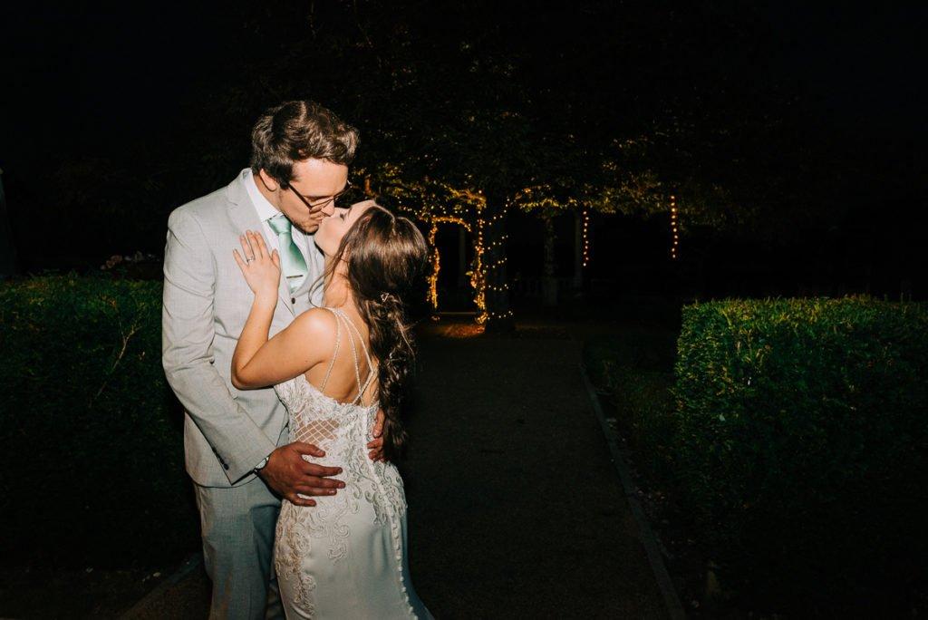 Kissing under a fairy light lit tree