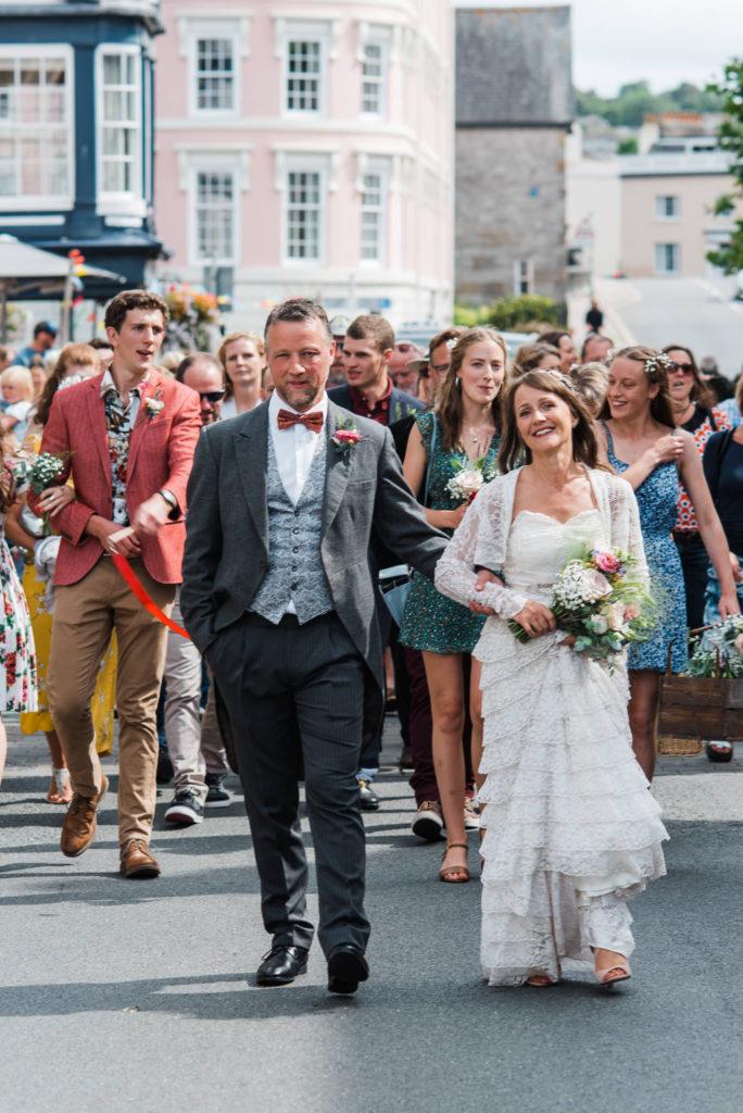 Bride and groom lead procession up Totnes highstreet