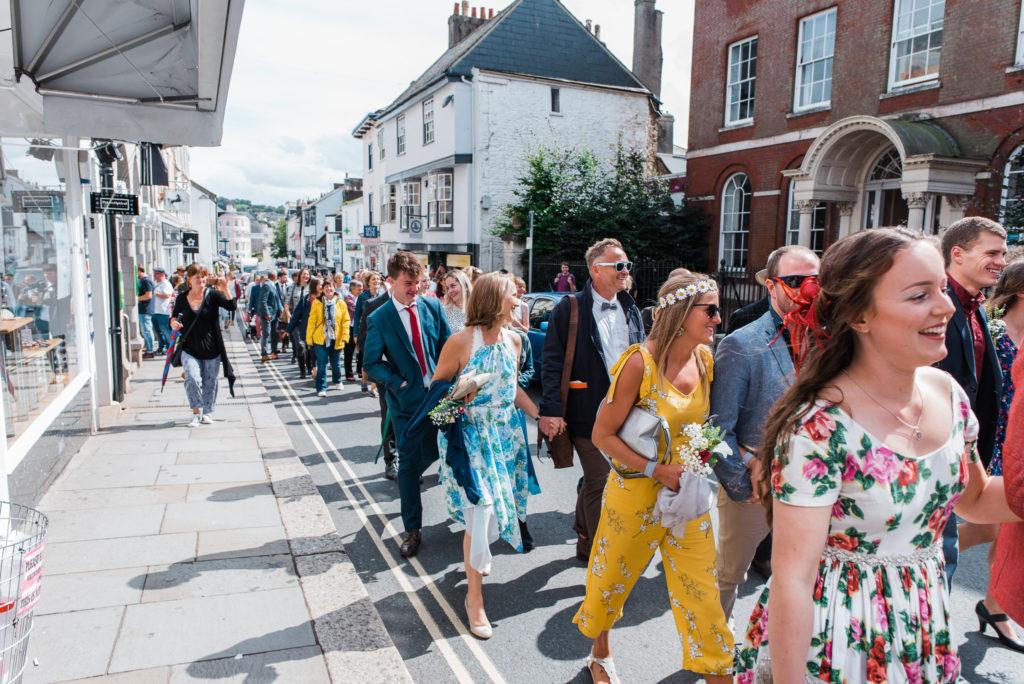 Wedding party proceed up Totnes high street