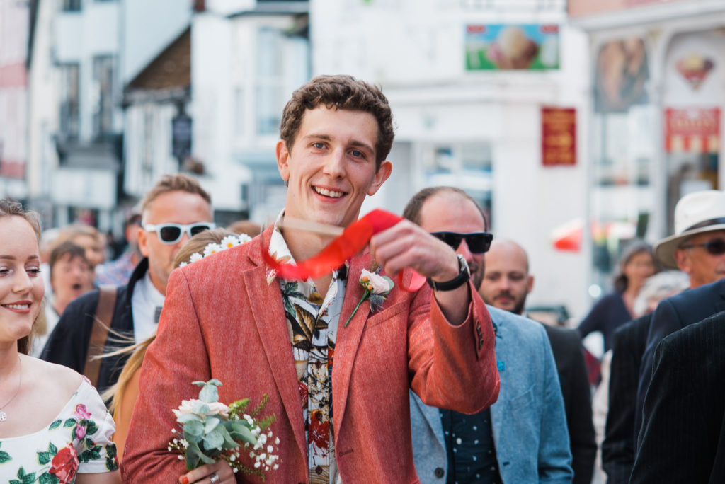 Fun Wedding guests wave ribbons up Totnes high street