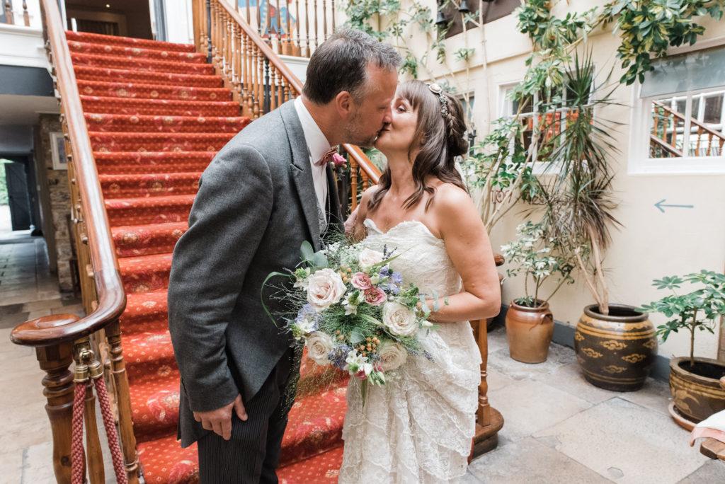 Bride and groom kiss before wedding ceremony in Totnes