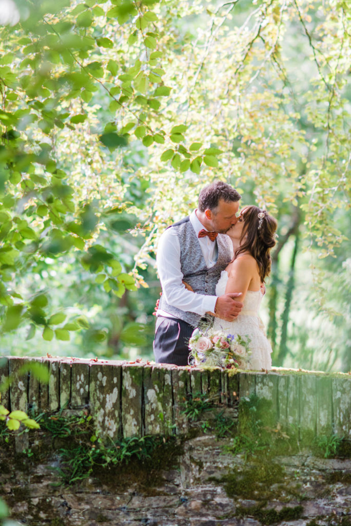 Bride and groom kiss on a bridge