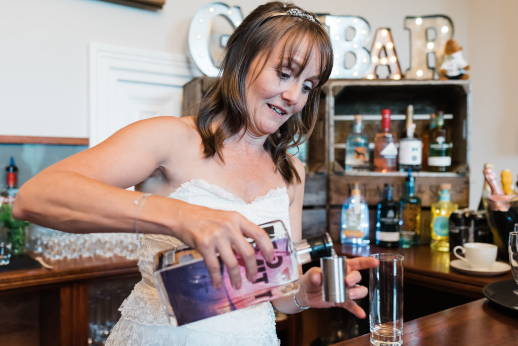 Bride pours gin for guests at wedding