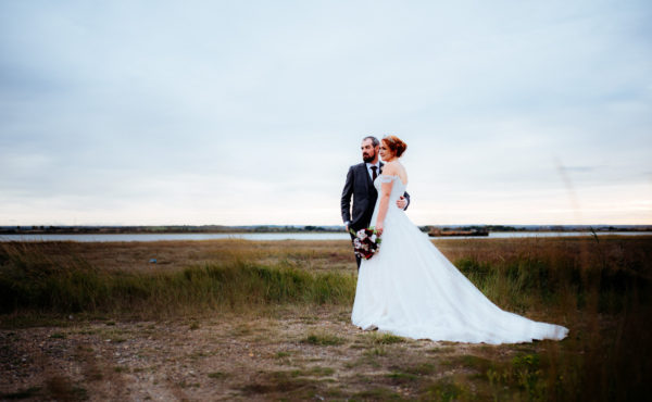 A bride and groom are photographed on a beach