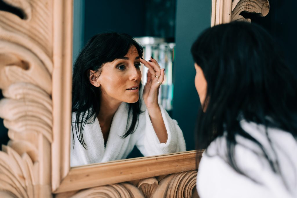 Bride checks her make up in the mirror