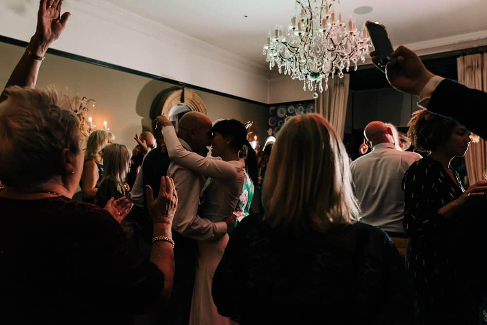 Friends and family dance with newlyweds